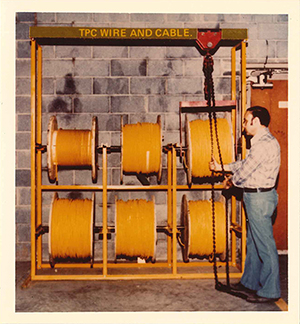 a man adjusting six reels of TPC cable in the Mentor warehouse and distribution center